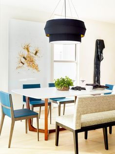 Modern dining room with a black pendant light and blue armchairs