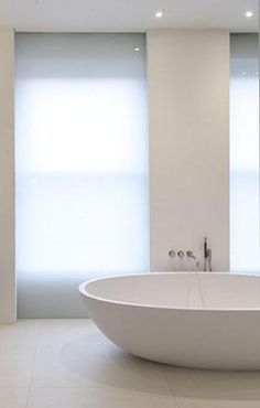 Minimal corian bathroom in London by McLean Quinlan, sliding laminated glass screens for control of light _