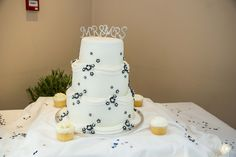 White 3 tier Wedding cake, with small blue colour schemed flowers.