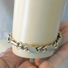 Bracelet chain link goldtone flat textured toppers size 6 3/4   Nice - curb chain is 1/4 inch wide, slightly flattened on top.  Closure is a foldover clasp and its all goldtone.  Decoration is made of