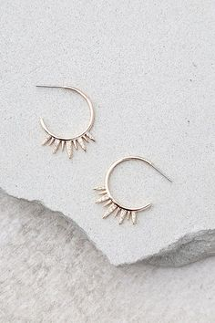 """The Shashi Lola Rose Gold Rhinestone Hoop Earrings make everyday a special occasion! 18k gold-plated hoop earrings detailed with rhinestone encrusted spikes. Earrings have a 0.75"""" diameter."""