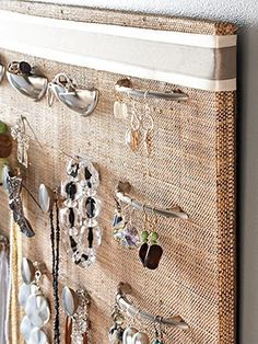 A cork board covered in a burlap sack accented with a little ribbon and the jewelry is hanging on dresser knobs.  Genius!