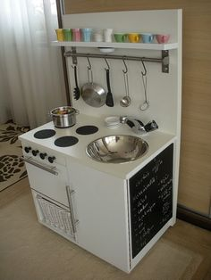 DIY modern play kitchen.  I love the hanging utensils , storage shelf and chalkboard on the side.