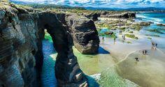 """Praia das Catedrais-Playa de las Catedrales. Durante la marea baja puede accederse a un largo arenal delimitado por una pared rocosa de pizarra y esquisto erosionada en formas caprichosas: arcos de más de treinta metros de altura que recuerdan a arbotantes de una catedral, grutas de decenas de metros, pasillos de arena entre bloques de roca. Con las """"mareas vivas"""" en las que las mareas bajan más y suben más que las mareas normales incluso se puede acceder a las playas vecinas por la arena."""