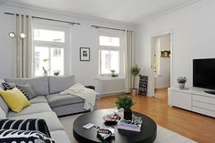 canapé gris, parquet et meubles blancs