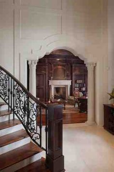 Ravelais: French Castle luxury home design by John Henry Architect Luxury house Foyer stair with iron railing