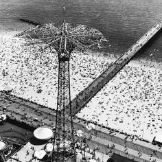"""From the April 14, 1952 photo essay """"A New Way To Look At The U.S — Camera and helicopter give an exalted view of the land."""" The original caption read: """"Beach Holiday dots the sands of Coney Island with New Yorkers out for sunshine. Slanting off to right from boardwalk is the big Steeplechase Pier. In foreground are the tower and wire guides of the amusement park parachute drop."""" (Margaret Bourke-White—The LIFE Picture Collection/Getty Images) #tbt #throwbackthursday"""