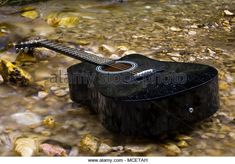 Black classic guitar on blurred water .