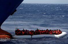 A rubber dinghy packed with migrants beneath the bow of a Panama-registered...