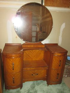 "Vintage wood vanity w/ round mirror, three vintage figurine lamps (no shades), decorative vanity items on tray, modern hair dryer. Five dovetailed drawer HW vanity on wheels, 43'Wx18""Dx29.5""H w/ matching round beveled glass mirror (detached), 29.5""diam x 33""H on wood base. Pr Victorian lady figurine lamps (no shades), third non-matching lady figurine lamp base, Revlon modern hair dryer, mirrored silver colored vanity tray 13.75""Lx9.25""W w/ vanity items incl green pitcher & bowl set by Avon…"