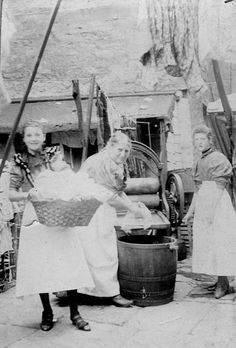 Old black and white photo of 3 women using a clothes mangle, one holding a basket of washing, are all smiling