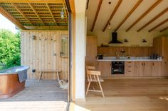 The patio is panelled in larch wood and the kitchen cabinetry in oak, helping to create a seamless transition between the two spaces, while a layer of clay render gives the interior walls a tactile, organic finish. Cabin Interiors, Rustic Interiors, Exeter, Cabana, Wood Interior Walls, Conception Durable, Modular Cabins, Modern Cabins, Outdoor Tub