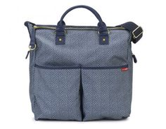Tote all of your baby's items in style with this Blue Pinpoint Signature Special Edition Changing Bag from Skip Hop!  This modern design boasts all of the features of the classic signature with a contemporary pattern. As with every Signature Changing Bag, a changing pad is included for on-the-go convenience. Magnetic closures on both the exterior bottle pockets and a zip on the main compartment ensure everything stays in its place. An interior bottle pocket and two side pockets keep…