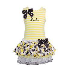 A simple yellow and white horizontally striped tank top is embellished with a bow of white on black polka dotted wide ribbon at the right shoulder, while a layered skirt of multiple fabrics composes the skirt of this adorable dress