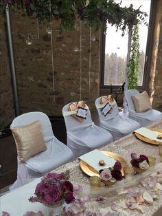 Hochzeit im Jagdschloss Platte mit Brauttischdekoration und Blumenranke als Hintergrund. Mit goldenen Platztellern.