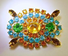 A Czech fruit salad brooch in multi color rhinestones, sparkly and vintage:  A real sparkler from an estate sale is this Czech vintage brooch with yellow, amber topaz, green and blue faceted rhinestones. Theyre clear with vivid color, and the back is unplated which is typical of vintage Czech brooches/pins. Four of the outer topaz rhinestones have open backs. The design is Art Deco and the pin is sturdy and straight...hardly any wear at all.  Length: 2 inches Width: 1-1/2 inches Hallmark…