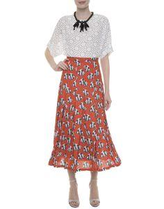 Top preto e branco gráfico, saia mídi laranja estampada Karin Feller, sandália listrada preta e branca, maxicolar preto.