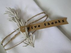 A lovely option to a keepsake napkin ring is this pretty napkin treatment with a rosemary or olive sprig