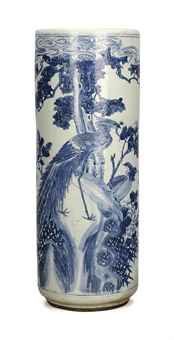 A CHINESE BLUE AND WHITE PORCELAIN UMBRELLA STAND DECORATED WITH PHOENIX AMONGST ROCKWORK,