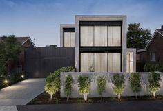 Minimalistisches Betonhaus mit Garage und Hecken an der Mauer