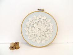embroidery hoop art with recycled vintage crochet flower doily on blue fabric