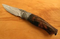 The blade is W2 heat treated with a hamon.    The guard and finial are damascus.    The handle is flame grained koa.