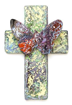 Waste from a demolished graffiti wall used to create 'On a Wing and a Prayer'. The butterfly and the cross unify to symbolize hope and new beginnings whilst the paint effect makes a statement about global decay.