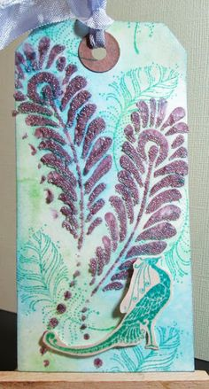 """Crafty Effusions. AND THEN - I had some coloured bead gel left over so I used another stencil and applied to a tag  (you can just see poking out above) later in the day I finished it off - using the Balzer Designs """"Peacock Feathers"""" stencil"""