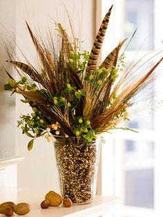 The natural look often is best left untamed and offbeat. This bouquet mixes faux greenery, ornamental grasses, and pheasant feathers with birdseed as filler.  Editor's Tip: Rather than filling the entire vase with birdseed, arrange the tall elements in a smaller vase and set inside a larger vase. Then fill the space between the two vases with birdseed.