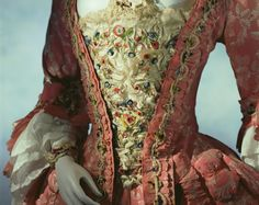 """PETO. Suiza. 1760- Material: Blanco Satén de seda con seda policromada, hilos de chenille y las flores de la franja marcha. El peto, un panel triangular en forma de V, llevaba en la parte delantera del vestido abierto de una mujer en el siglo 18. Para mantener el pecho saliendo desde parado, el peto estaba adornado con bordados extravagantes, encajes, las filas de arcos de la cinta llamada """" échelle""""(escalera) y, a veces con piedras preciosas."""