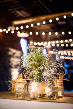 Baby's breath flower centerpieces in Mason Jars. Pretty for a rustic or backyard wedding!