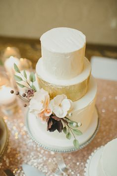 gold painted cake with sugar flowers, photo by Mango Studios http://ruffledblog.com/ontario-flower-child-wedding #weddingcake #cakes #romantic