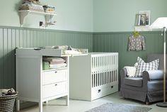 IKEA kid room / キッズのチェンジングテーブル、ベビーベッド、アームチェア、ラグ、フロアランプが設置されたベビールーム。