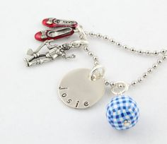 This is a cute Wizard of Oz charm necklace that is custom and personalized. Were off to see the Wizard! The .75 disc is made of aluminum and is hand stamped with the name or saying of your choice. It is paired with a ruby red slippers charm, a pewter charm of your choice and a matching blue and white gingham bead. A 14 silver ball/bead chain is included. If you would like a longer length, just let me know at checkout.  *Handcrafted from aluminum *Each letter or heart is individually stamped…