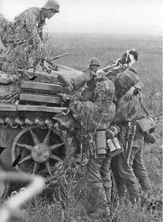 German soldiers help a wounded comrade onto a Panzer III tank.