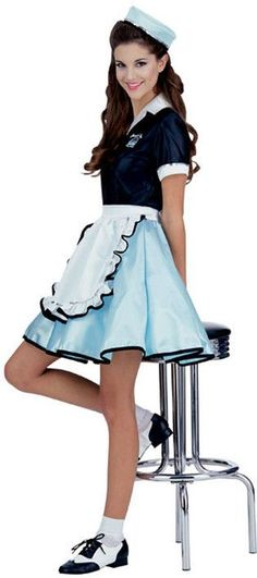 #15917 The Car Hop Girl Costume includes a uniform dress featuring a dark blue collared top and light blue skirt with black trim. The included apron and cap complete the car hop costume. Includes: - C