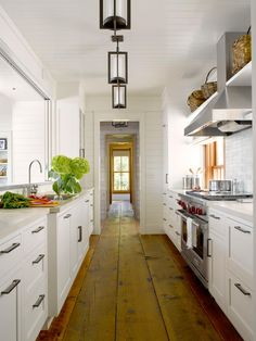 Wall-to-ceiling white paneling makes this galley kitchen feel bright and inviting. White cabinets pair with stainless steel appliances for a classic look, while reclaimed wood floors add rustic appeal.  The floor, so stunning.