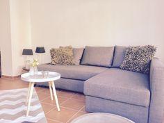 Gemütliches Sofa In Grau Mit Flauschigen Kissen Laden Zum Entspannen Ein.  Dazu Terra Cotta Fliesen