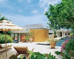 """The residence is """"far from the island's nervous energy,"""" says Liz Claiborne of her Pierre Monsaingeon–designed Caribbean residence. The east terrace is used for sunbathing. A curved ocher wall formed from polished concrete screens the outdoor shower, and the area is dotted with various French pottery pieces."""