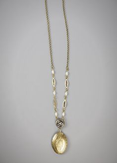 An American-made oval locket dangles from one authentic antique button, circa 1880-1910, in this romantic necklace, which is a graceful 31 inches long. Also features Czech glass rice pearls and vintage wire filigree connectors. We will choose a lovely button from our extensive collection to make your necklace.