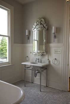This marble sink looks classic with a Venetian style mirror and Carrara marble basketweave floor. The frame supporting the marble top and sink is called a sink stand or wash stand.