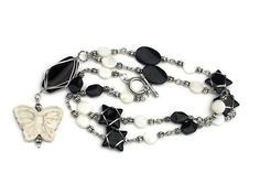 Long black glass beads, white mother of pearl and silver toned necklace with white butterfly howlite focal bead.  Silver tone toggle clasp.