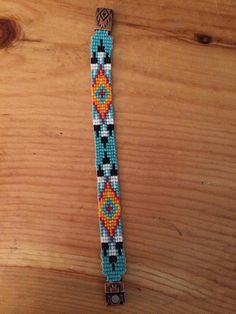 5/8th inch Turquoise and feather loom beaded bracelet with magnetic copper Aztec closure. Handmade using glass beads.