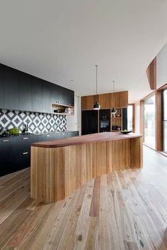 un îlot en bois au design élégant et des armoires noires dans la cuisine moderne