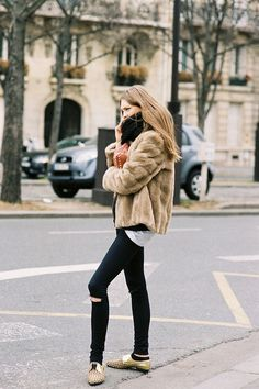 model street style: spiked bag & shoes, faux fur jacket.