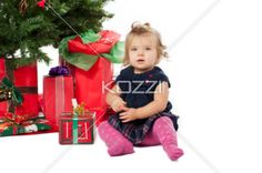 portrait of a sweet girl sitting by christmas tree and christmas gift box. - Portrait of a sweet girl sitting by Christmas tree and Christmas gift box over white background. Model: Hannah Phillips