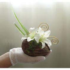 Nature et original, ce porte alliance sera idéal pour un mariage au thème exotique. Réalisé à partir d'une noix de bouddha, ce coussin d'alliance est orné de fleurs de lys et de mousse végétale. Vous pourrez y maintenir vos alliances grâce à deux arabesques.