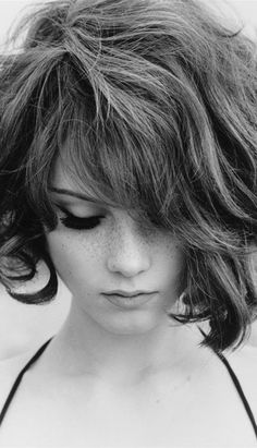 this is a great photo. The contrast between her hair and her skin is perfect. the girl in the photo looks like she isn't very confident and sad. She is thinking about something or someone.