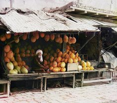 1911 Dressed in traditional Central Asian attire, a vendor of locally grown melons poses at his stand in the marketplace of Samarkand in present-day Uzbekistan.