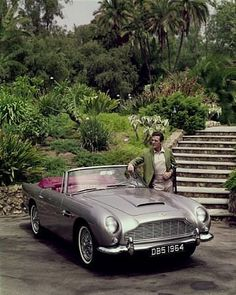 ROBERT STACK AT HOME IN BEVERLY HILLS CA. WITH HIS 1964 ASTIN MARTIN DB5, 1964